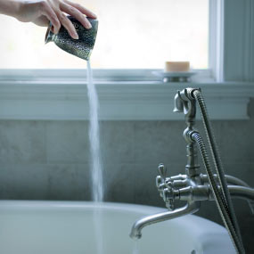 A person pours salts into a bathtub
