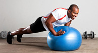 man in pushup position with stability ball