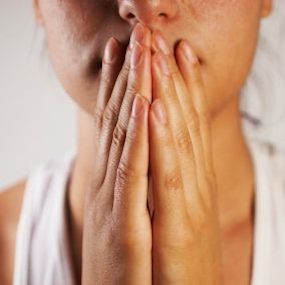 A woman holding her hands to her face pensively.