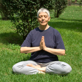 A woman meditating in a park.