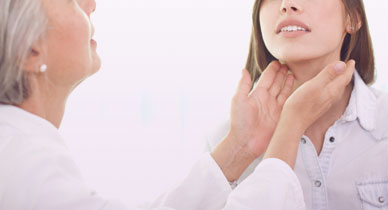 doctor checking woman's thyroid gland