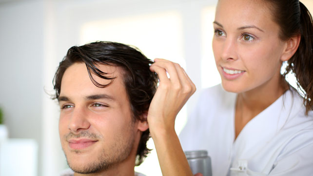 woman applying castor oil to man's hair