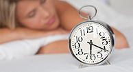alarm clock and sleeping woman