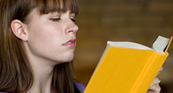 woman straining to read because of farsightedness