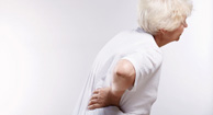 elderly woman holding her back