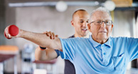 elderly man lifting weights with a personal trainer