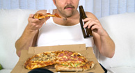 man binging on pizza and beer