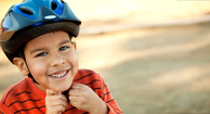 boy putting on bicycle helmet