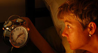 woman with OAB looking at her alarm clock