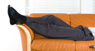 man elevating legs on sofa
