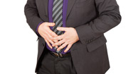 businessman in suit grabbing his stomach
