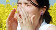 woman sneezing in a field