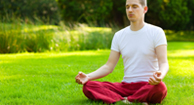 A man performing breathing exercises in the park.