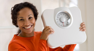 happy woman holding a scale