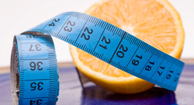 A measuring tape around an orange