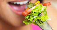 A girl eats a forkful of salad.
