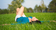 A woman with menopause lying in the grass relaxing.