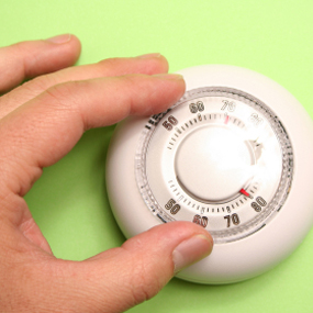 Woman turning the thermostat