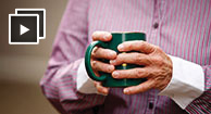 arthritic man holding cup of herbal tea