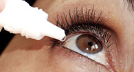 person using eye drops