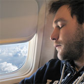 Young man sleeping on a plane.